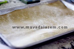 کاغذ پوستی مخصوص شیرینی پزی را در قالب میگذاریم و روی آن آرد می ریزیم