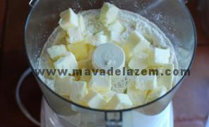 آرد و شکر و نمک را مخلوط میکنیم و بعد تکه های کره خرد شده را به آن اضافه کرده و در میکسر مخلوط میکنیم