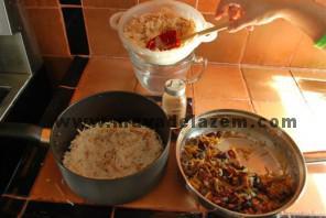 بعد از اینکه ته دیگ دلخواه خود را در قابلمه گذاشتید لایه لایه برنج و مواد تفت داده شده و ادویه پلویی میزنیم